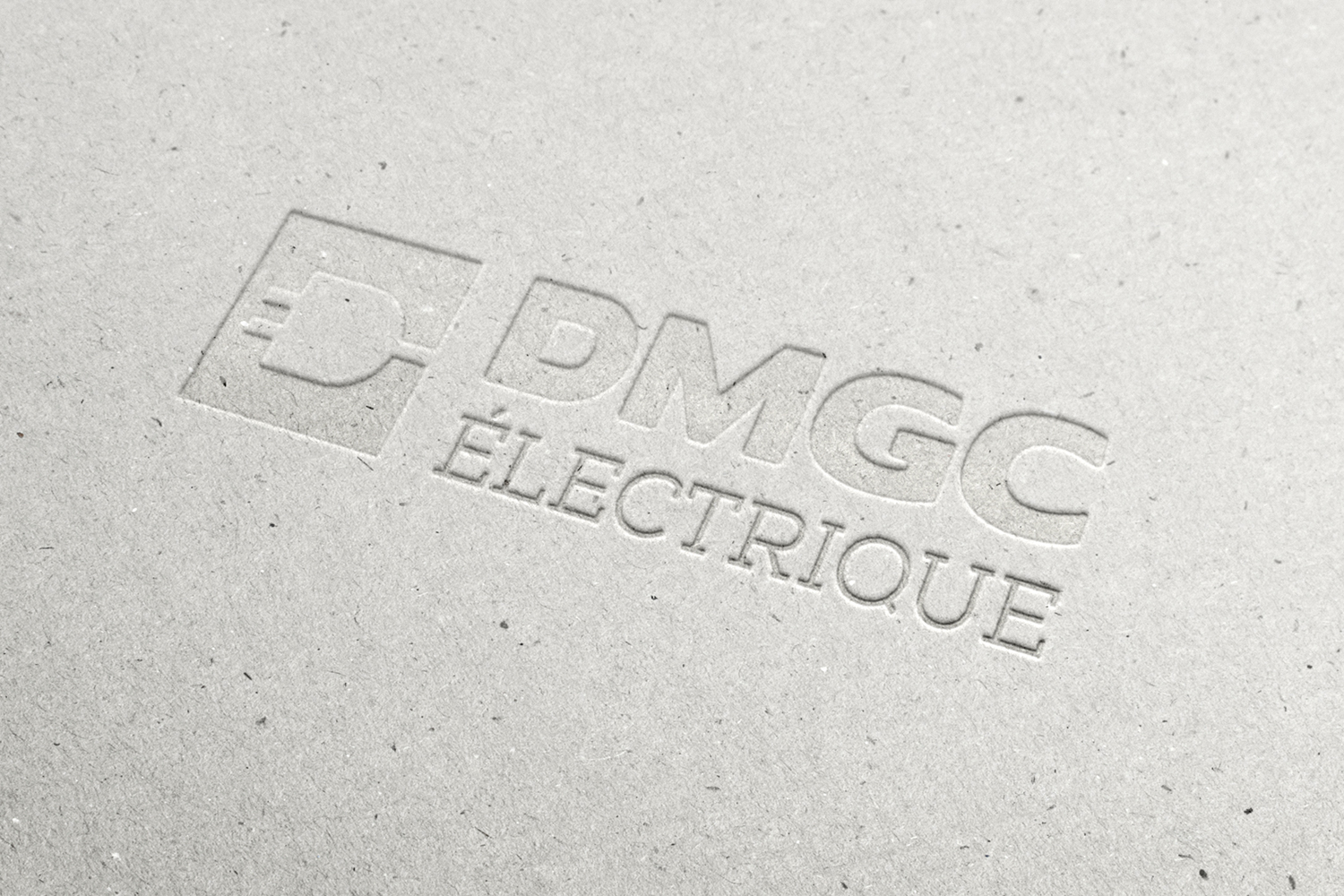 dmgc electrique's logo debossed into a grey recycled cardboard, simple, no ink, letterpress, branding, print design