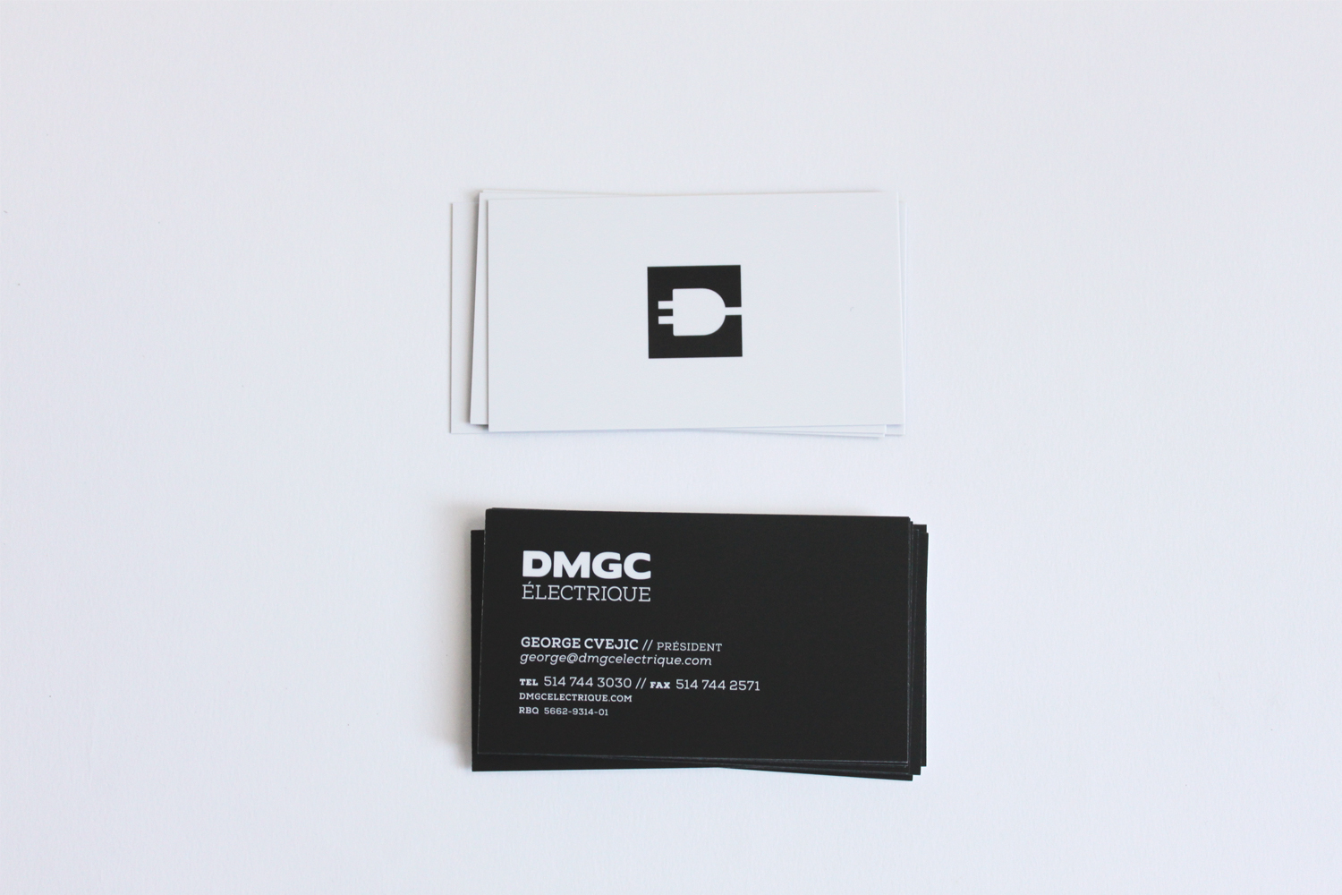 front and back view of dmgc electrique's business card design, black and white, simple, spot uv with logo only, overhead view, print design, branding