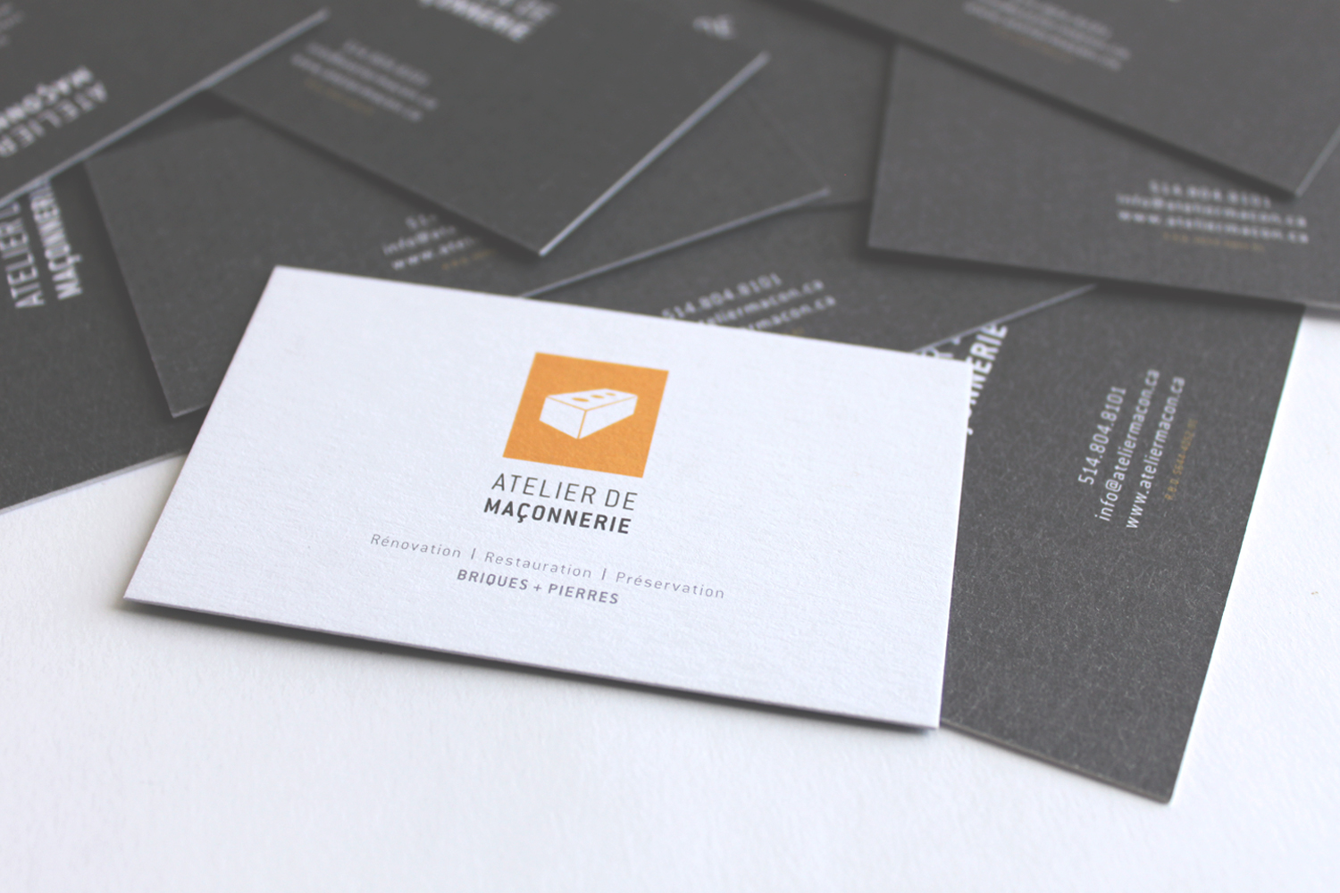 closeup of atelier de maconnerie's business card design, front and back, white, grey, orange, simple, subtle geometric background pattern, logo design, print design