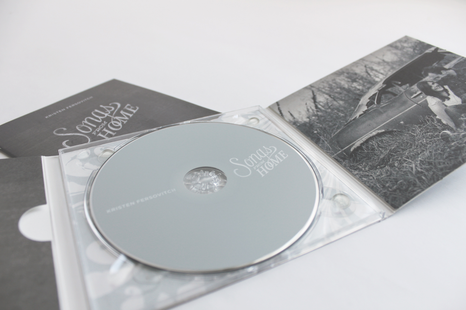 kristen fersovitch songs from home album layout, closeup of disc and booklet, hand lettered logo, blue and grey, soft, album design, digipack, cd packaging, print design, uncoated paper